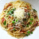 bowl of spaghetti with bacon, peas and chilies