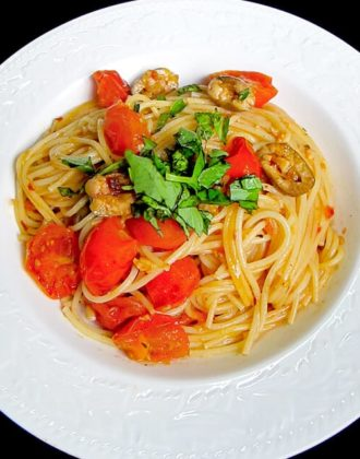 bowl of spaghetti with cherry tomatoes and basil