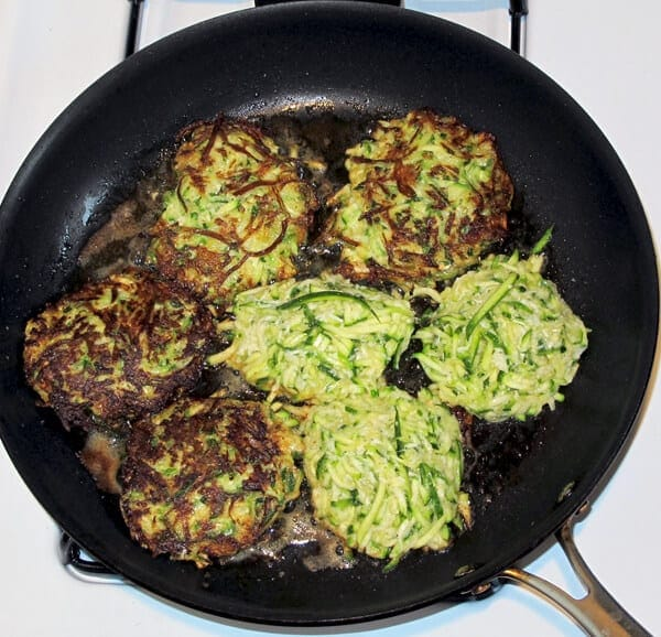 zucchini cakes frying in a pan