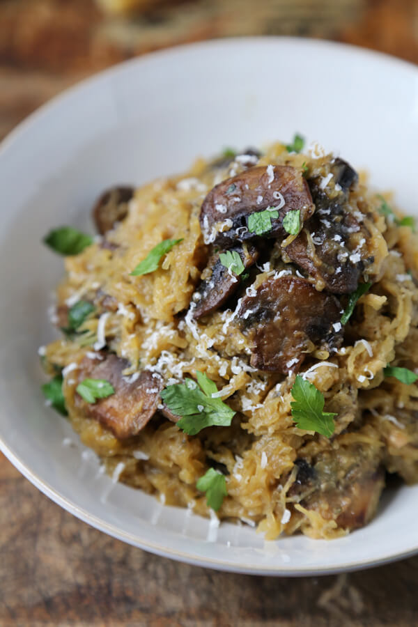 Bowl of oven shredded spaghetti squash with caramelized mushrooms.