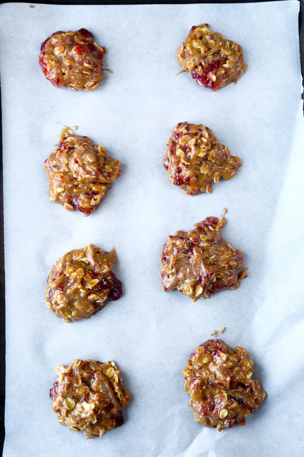 Gluten-free goodness! Chewy, sweet and fruity, these gluten-free peanut butter and raspberry jam cookies are so good you won't be able to stop at just one! #glutenfreecookies #glutenfreerecipes #flourless #homemadecookies | pickledplum.com