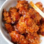 General Tso Chicken - A General Tso Chicken recipe that's baked, not fried and so much better than the real thing! Crispy and tender chicken pieces baked in crushed cornflakes and dressed in a classic sweet and sour sauce. #chinesefood #chickenrecipes #homemade #healthy #bakednotfried | pickledplum.com