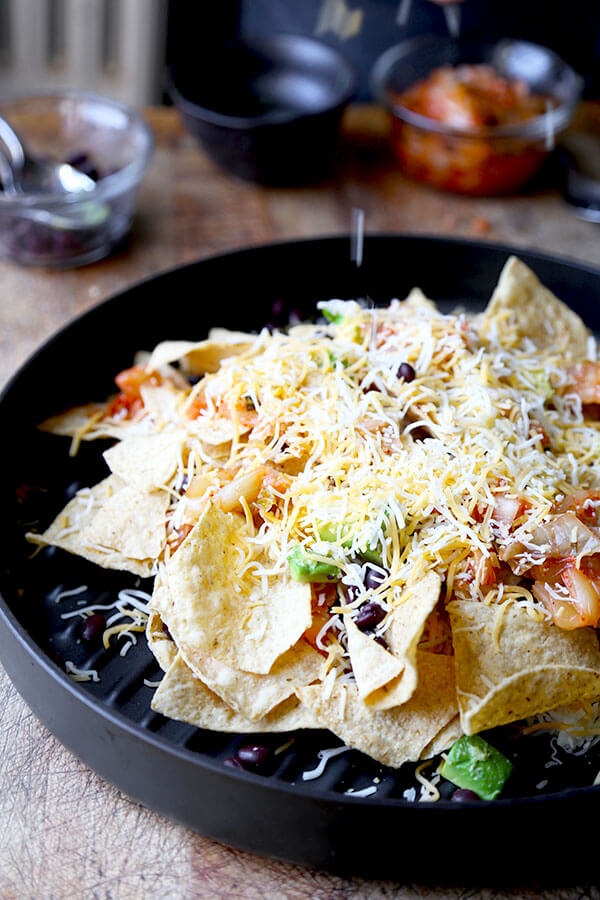 Loaded Nachos With Kimchi And Miso Crema - Six minutes in the oven is all it takes to transform this Loaded Nachos with Kimchi and Miso Crema Recipe into a spicy, cheesy and delicious snack! Recipe, snack, tortillas, superbowl, barbecue, chips | pickledplum.com