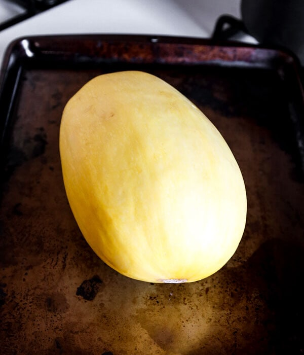 whole spaghetti squash on a baking tray.