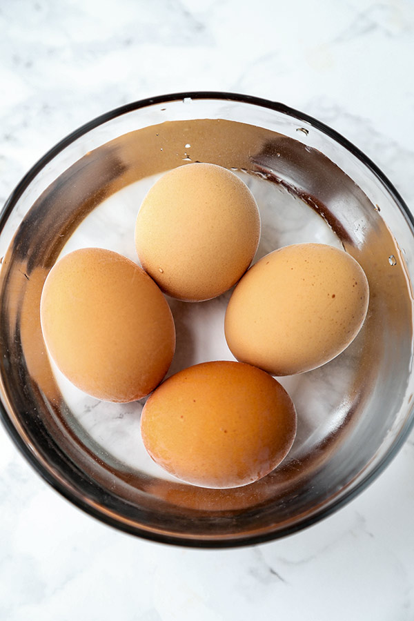 Cooked eggs in ice bath.