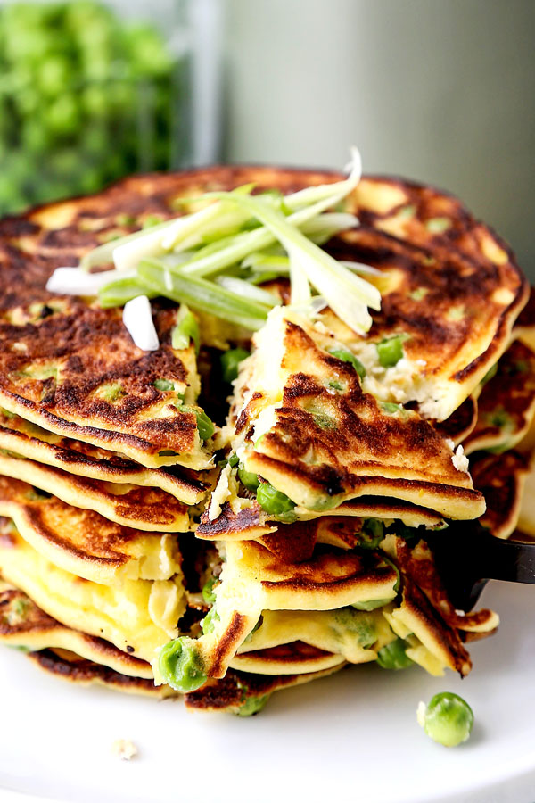 Spring Pea Pancakes - A bright and pillowy soft Spring Pea Pancakes Recipe. These small savory pancakes have the verdant pop of fresh green peas. Find out how to choose the best fresh peas - and info on frozen vs fresh spring peas. It's springtime on a plate! #pancakes #healthyeating #brunch #peas | pickledplum.com