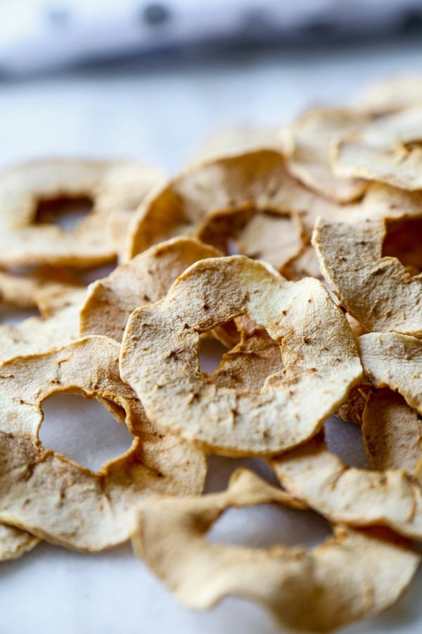 Homemade Baked Apple Chips - Learn how to make easy, crispy baked apple chips in an oven (no dehydrator needed!) This is a healthy snack for kids and for weight loss. 100% natural, no sugar added. #veganrecipe #applerecipe #healthysnack #vegetarian #plantbased #kidfriendly #healthybaking | pickledplum.com