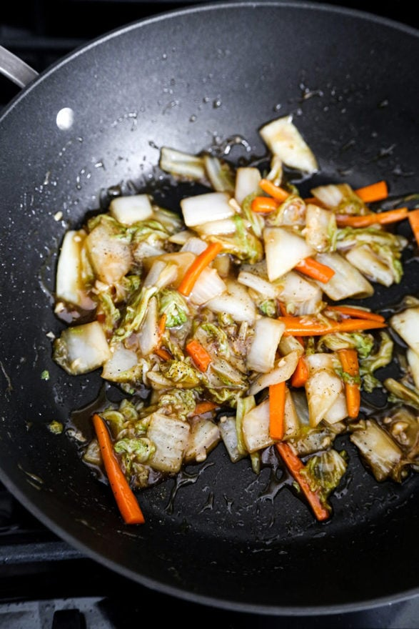 Stir frying napa cabbage in wok