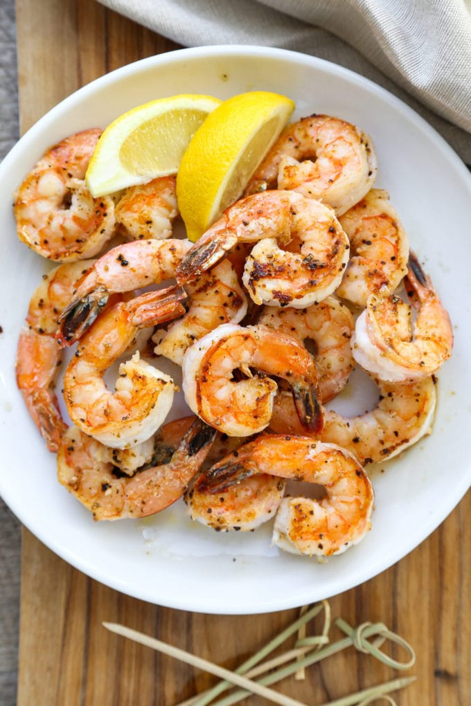 plate of garlic shrimp with lemon wedges